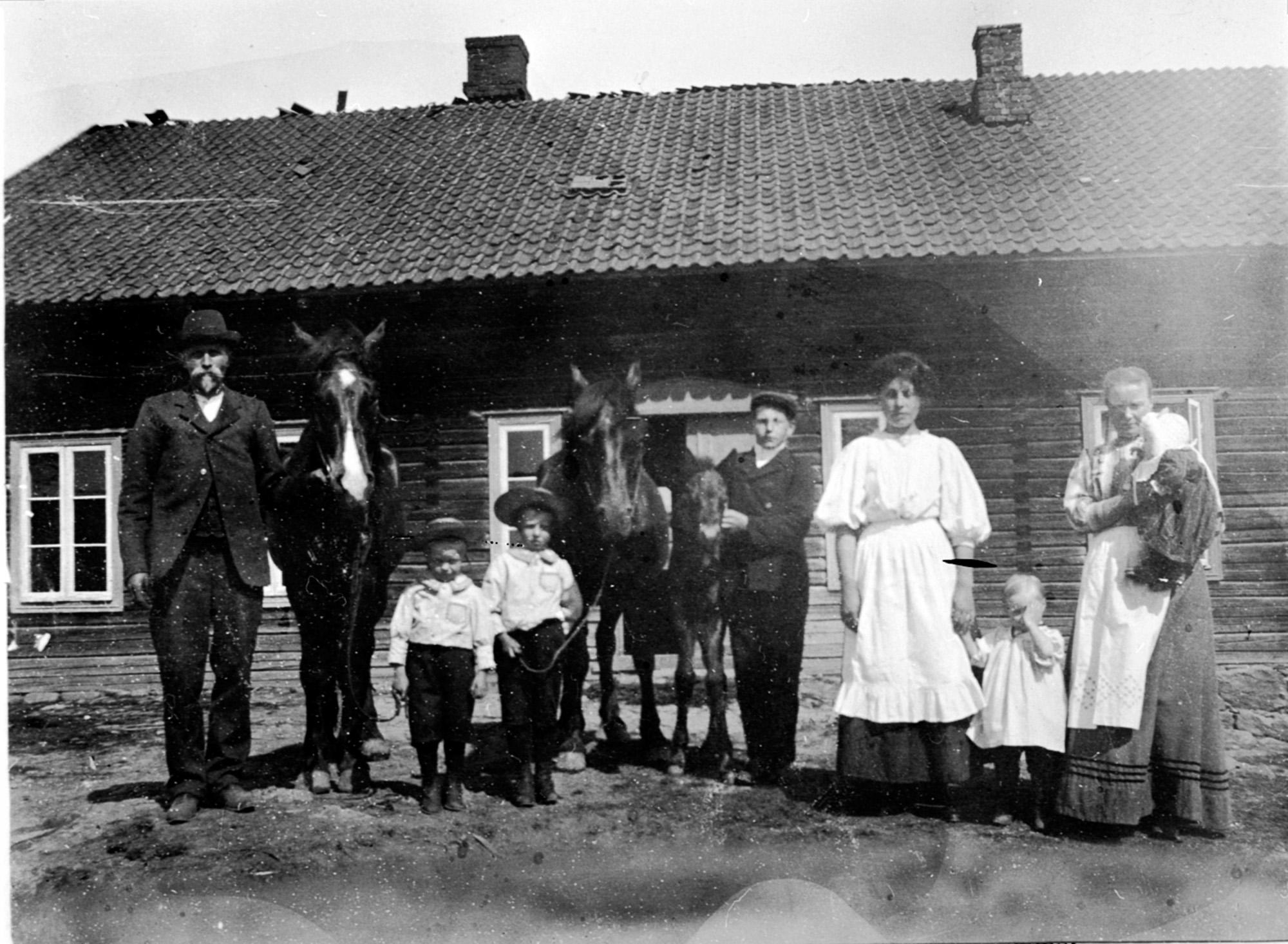Bilde av mennesker foran hus