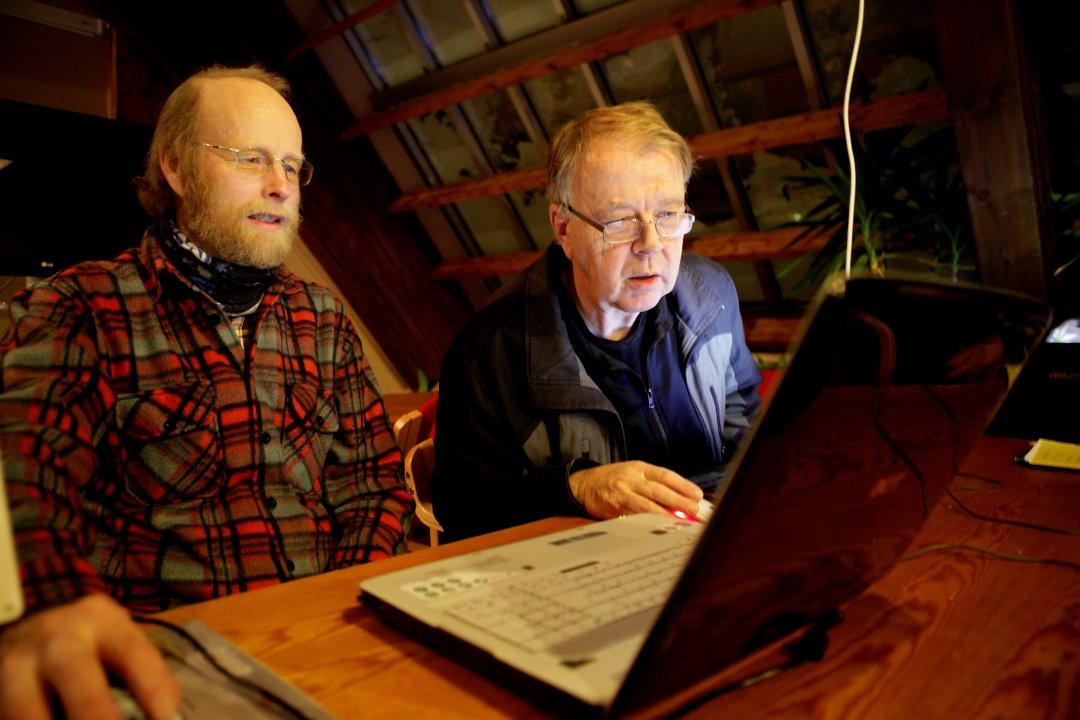 To personer som hjelper hverandre med slektsforskning foran en PC.